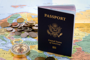 USA passport, compass and foreign coins sit on a map of Europe for an international travel concept.
