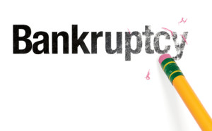 Close up of a yellow pencil erasing the word, 'Bankruptcy.' Isolated on white.