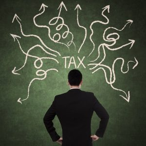 Concept of businessman thinking with arrows coming from tax