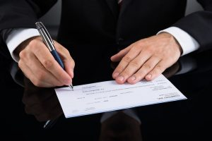 bigstock-Businessperson-Signing-Cheque-100578386-300x200